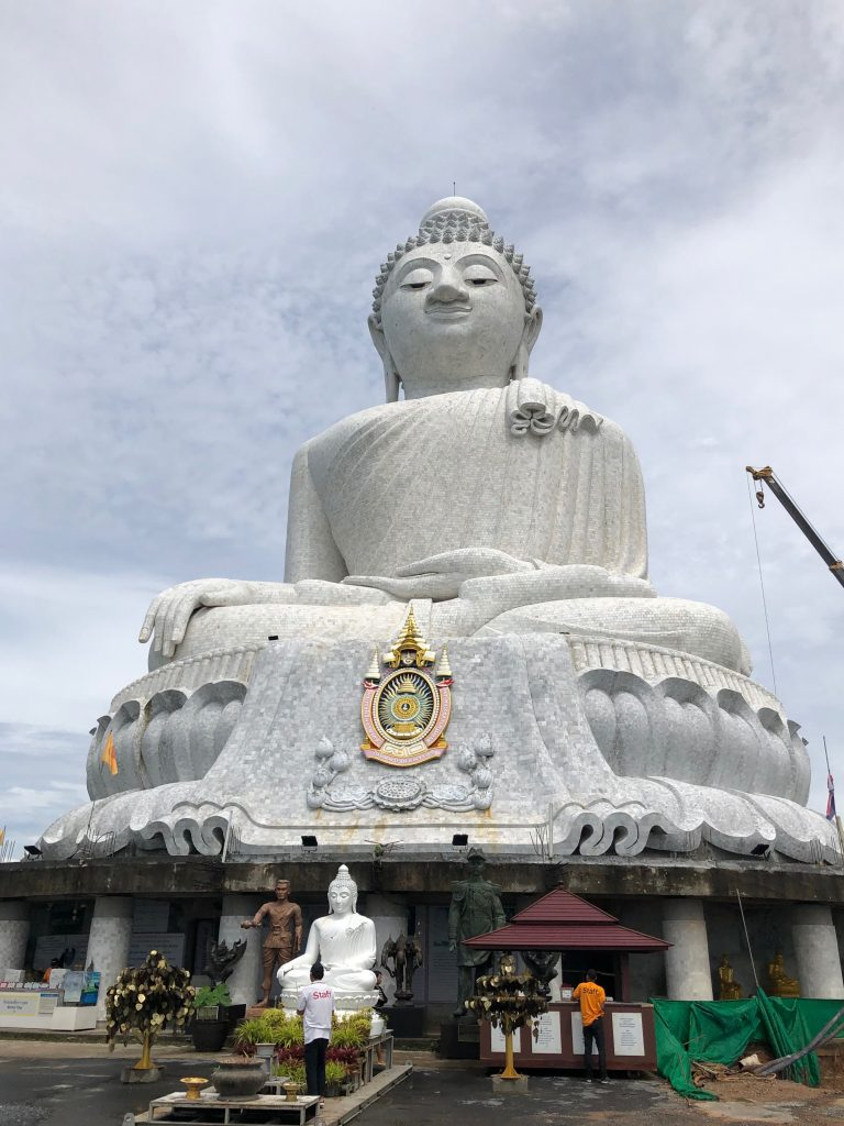 A giant pale grey Buddha sits against a pale blue cloudy sky