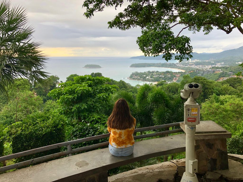 A girl sits on a curved bench at the forefront of the photo facing away from the camera. She is looking out at a view of leafy green jungle and a curved bay which juts into the sea