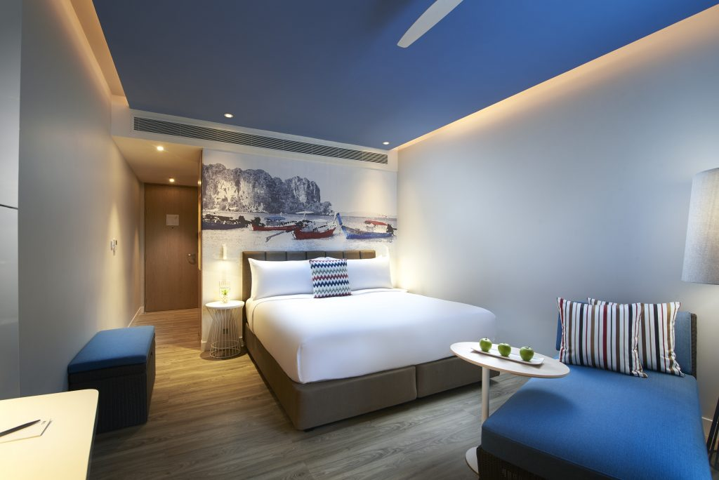 A hotel room containing a blue day bed close to the camera and a double bed with white bedding and a white, blue and red throw cushion
