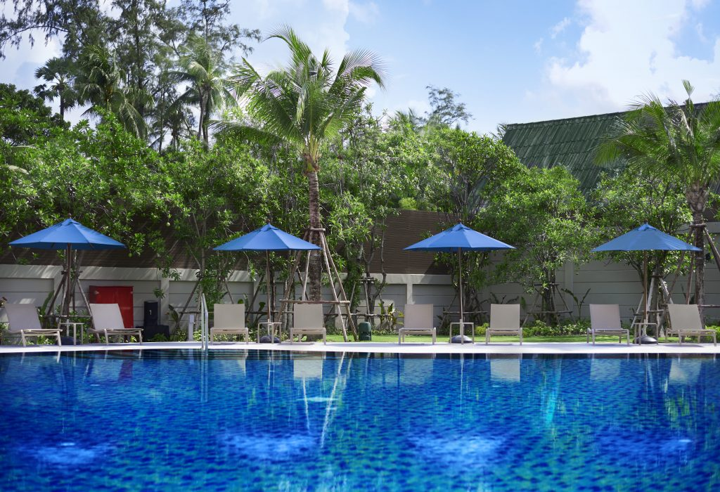 A blue swimming pool surrounded by sunloungers and blue parasols