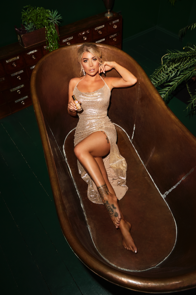 Olivia Buckland, in a tight gold sequin gown, poses seductively in an empty copper bath. She has glowing bronzed skin and is displaying a bottle of Cocoa Brown tanning oil in her hand