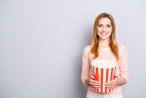 Bowl people freetime fashion beauty trend style stylish people person concept. Portrait of excited cheerful glad attractive woman watching tv eating pop corn from big box isolated on gray background