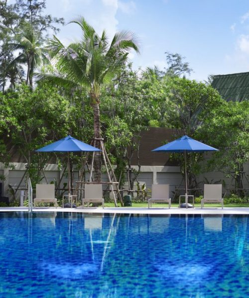 The swimming pool at OZO Phuket, showing the poolside sun loungers and blue parasols
